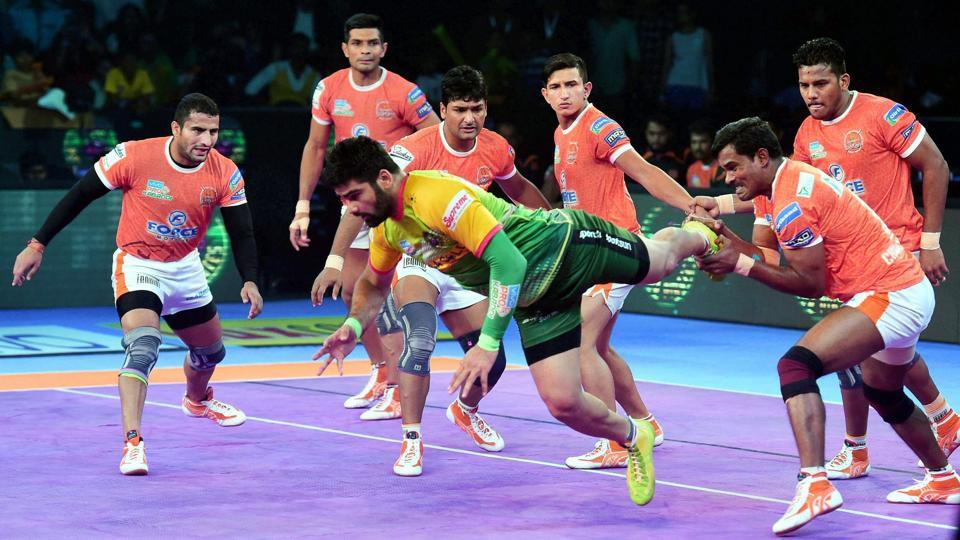 Pardeep Narwal in Green jersey of Patna Pirates is pinned down by Puneri Paltan players during their  Pro Kabaddi league match.
