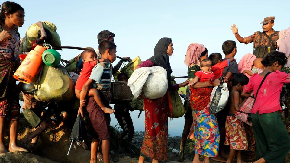 Rohingya refugees arrive at the Bangladeshi side of the Naf river after crossing the border from Myanmar on October 16.