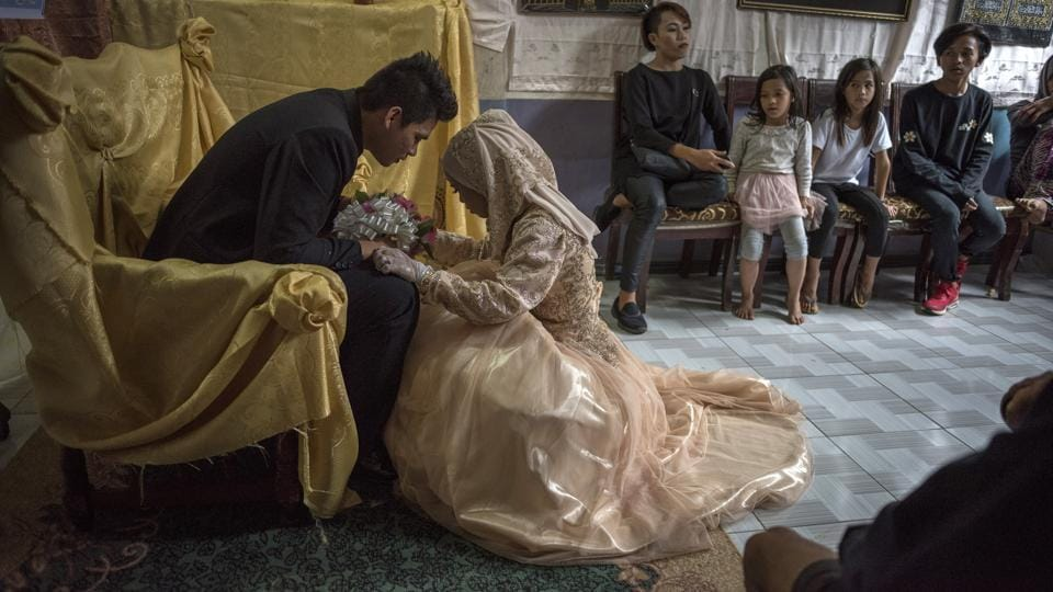 Bride Katty Malang Mikunug (R ), kneels before Paulo Mamayo Ambor, 22, during their wedding on October 21, 2017, in Saguiaran, southern Philippines. Paulo, a resident of Marawi who was displaced by fighting between government troops and IS-inspired militants, wed Katty Mikunug, a resident of an adjacent town in Saguiaran. (Jes Aznar / Getty Images)