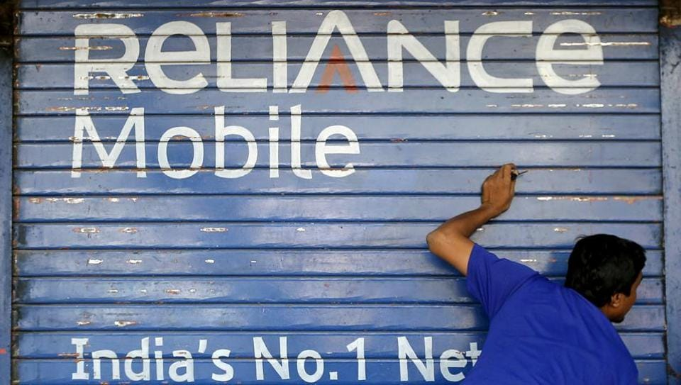 A man opens the shutter of a shop painted with an advertisement of Reliance Communications in Mumbai, India, November 3, 2015.