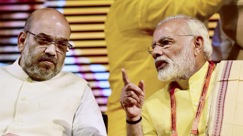 Prime Minister Narendra Modi talks with BJP president Amit Shah at party's national executive meeting at Talkatora stadium in New Delhi.