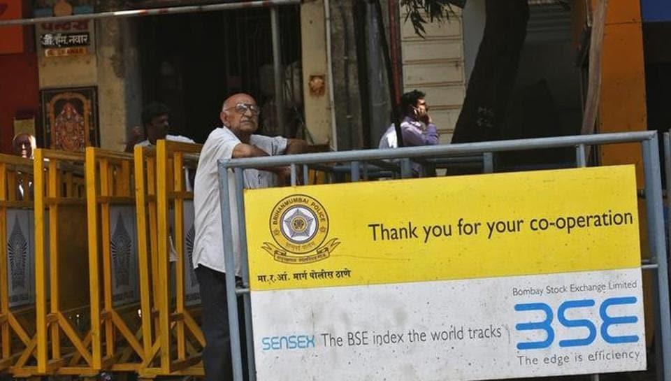 A man looks at a screen across the road displaying the Sensex on the facade of the Bombay Stock Exchange (BSE) building.