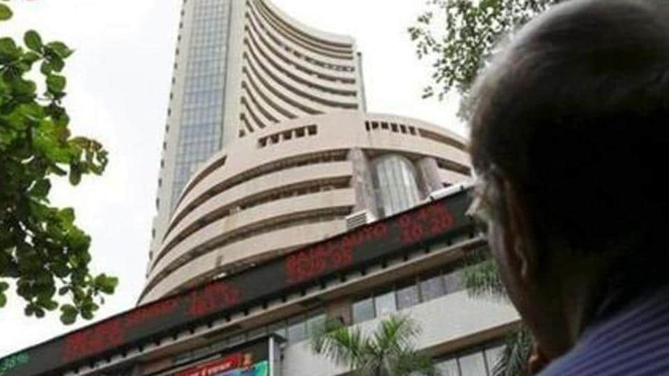 A file photo of a man looking at a screen across a road displaying the Sensex on the facade of the Bombay Stock Exchange (BSE) building in Mumbai.