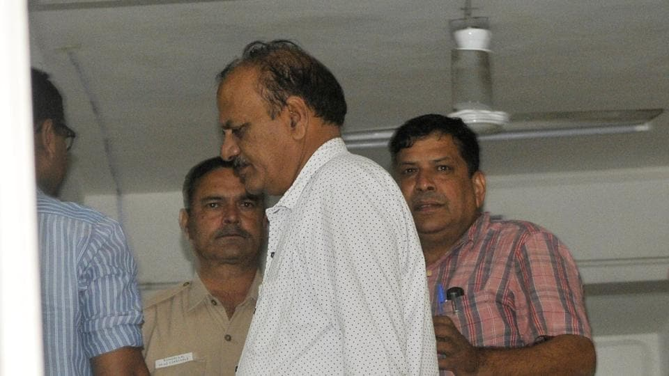 Mohan Singh (in white shirt) arrested by the CBI at the Sector-31 police station on Tuesday.