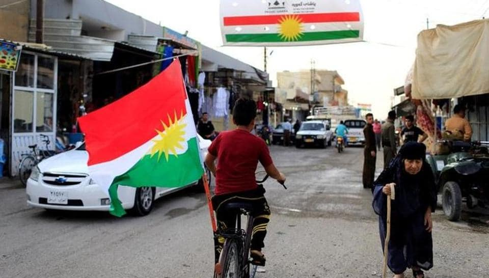 A boy rides a bicycle with the flag of Kurdistan in Tuz Khurmato, Iraq September 24, 2017.