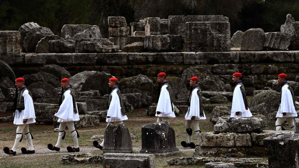 Greek Presidential guards, or Evzones, walk across the ancient archaeological site during the lighting ceremony of the Olympic flame. The traditional ceremony, introduced for the first time during the 1936 Berlin Olympics, did not benefit this time from the Greek sun playing a spoilt sport. (Aris messinis / AFP)