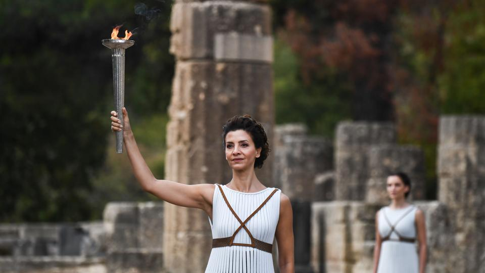Katerina Lechou (L), acting the high priestess, holds the Olympic flame at the Temple of Hera. From the rain-soaked valley of Ancient Olympia, where the Games of antiquity were held for more than a thousand years, the flame will course through Greece for eight days and reach South Korea on November 01,  2017. (Aris messinis / AFP)