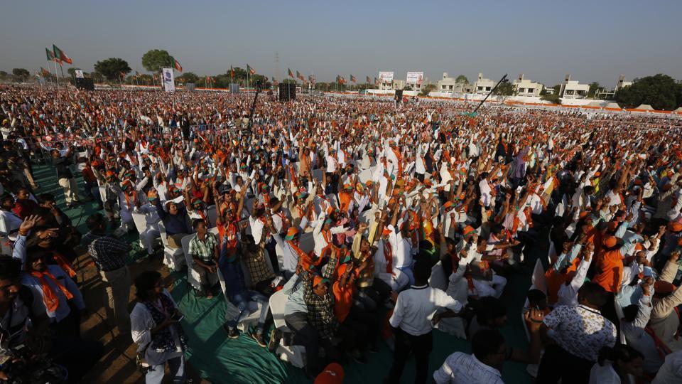 BJP supporters raise their hands during the Gujarat Gaurav Maha Sammelan in Gandhinagar.