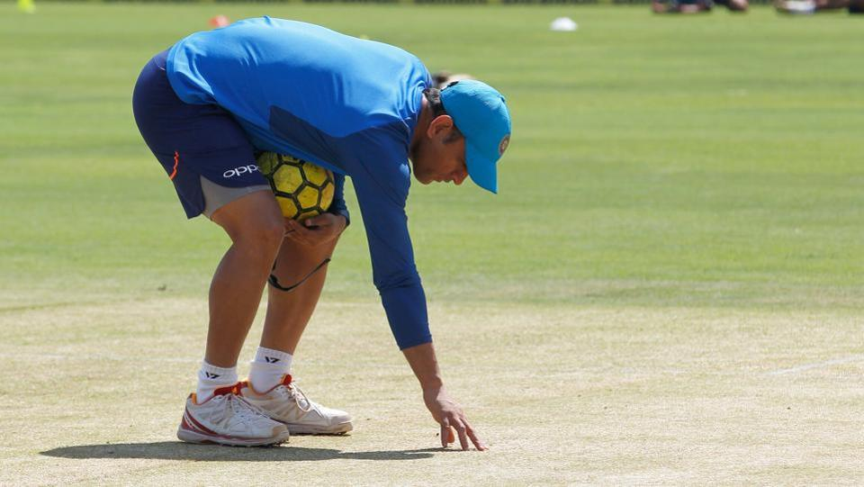 MS Dhoni inspects the pitch in Pune ahead of the India vs New Zealand 2nd ODI. Pune pitch curator Pandurang Salgaonkar has been charged with pitch-fixing by BCCI bosses.