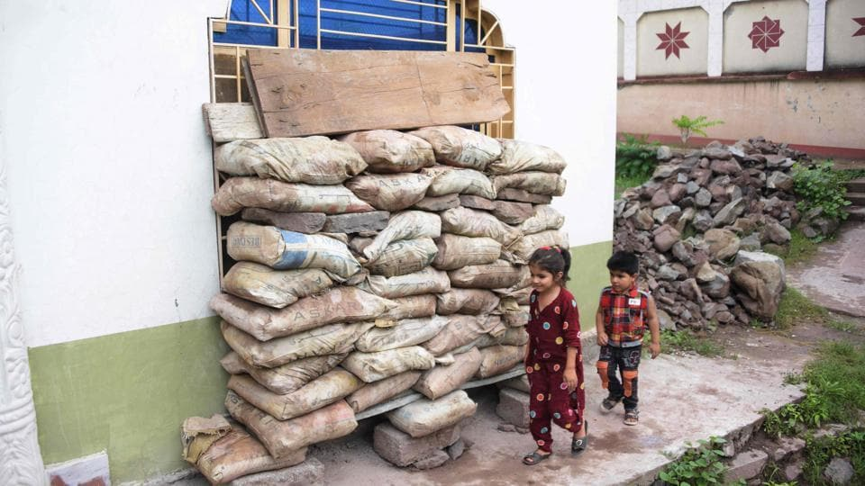 Children walk past a window covered with mud bags to protect from bullets after cross-border firing between Pakistan and Indian troops in Morha village Line of Control (LOC) in Nakyal Sector, 140 kilometres from Muzaffarabad on July 22.