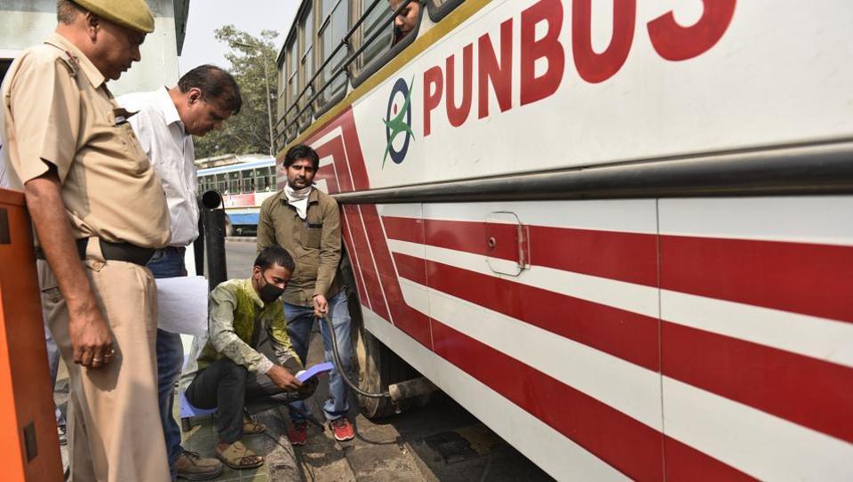 Delhi transport department officials check passenger buses for pollution at ISBT Kashmere Gate.