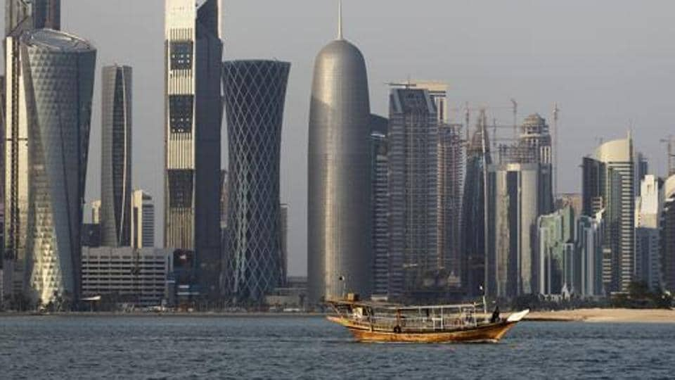 A traditional dhow floats in the Corniche Bay of Doha, Qatar, with tall buildings of the financial district in the background.