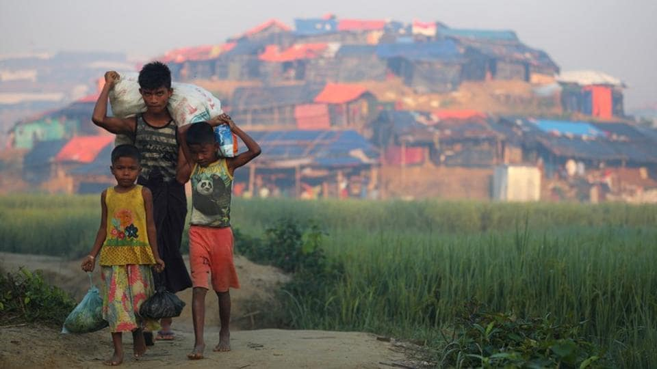Rohingya refugee children carry supplies with Balukhali refugee camp seen on a hillock near Cox's Bazar on October 23, 2017. More than 300,000 children are among the refugees. Mark Lowcock, U.N. humanitarian coordinator, announced that many were acutely malnourished. (Hannah McKay / REUTERS)