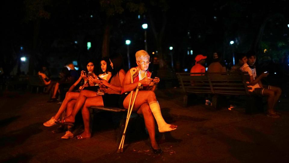 People connect to the internet at an outdoor hotspot in Havana, Cuba. At dusk, when the worst of the Caribbean heat has subsided, parks around Cuba fill with families video chatting with loved ones abroad or scrolling through social media --their animated faces lit by telephone and tablet screens. (Alexandre Meneghini / REUTERS)