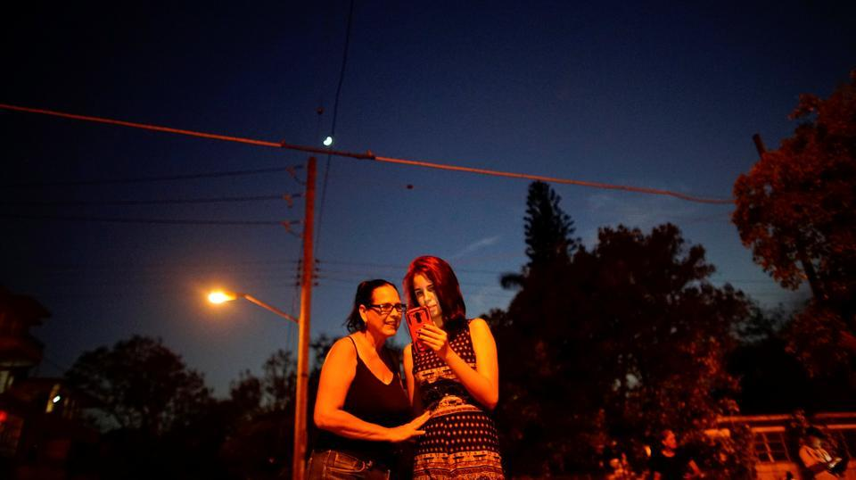 Claudia Espinosa, 20 (R), and her mother Maribel Sosa, speak to relatives in the US at a hotspot in Havana. 'A lot has changed,' said 54-year-old Sosa, having stood for an hour at the corner of a park, laughing and gesticulating at her phone's screen. She recalled how queuing all night to use a public telephone to speak with her brother for a few minutes after he emigrated to Florida in the 1980s. (Alexandre Meneghini / REUTERS)