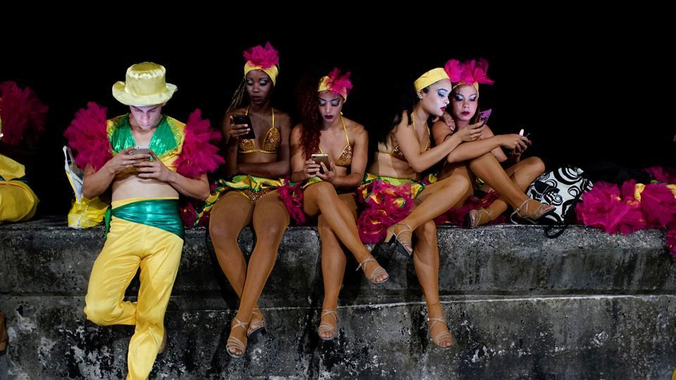 Dancers use an internet hotspot before performing at the Carnival of Havana. Given the relative expense of connecting to the internet, Cubans use it mostly to stay in touch with relatives and friends. Although prices have dropped, the $1.50 hourly tariff represents 5% of the average monthly state salary of $30.  (Alexandre Meneghini / REUTERS)