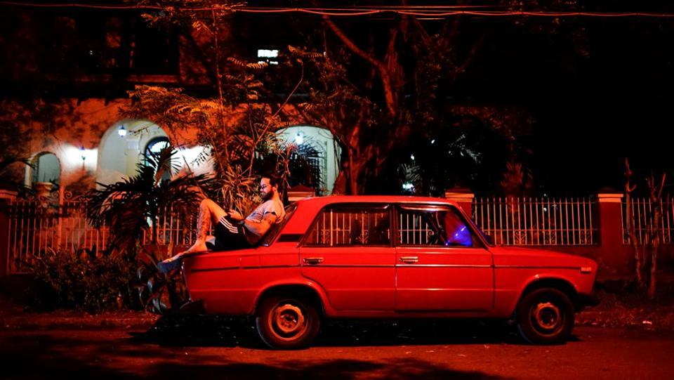 Tourist guide Daniel Hernandez, 26, sits on his Russian-made car speaking to his girlfriend who lives in Britain, at a hotspot in Havana. 'There's absolutely no privacy here,' said Hernandez. 'When I have sensitive things to talk about, I try shutting myself into my car and talking quietly.' (Alexandre Meneghini / REUTERS)