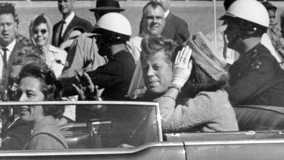 President John F Kennedy waves from his car in a motorcade in Dallas. Riding with Kennedy are First Lady Jacqueline Kennedy, right, Nellie Connally, second from left, and her husband, Texas Governor John Connally, far left on November 22, 1963.