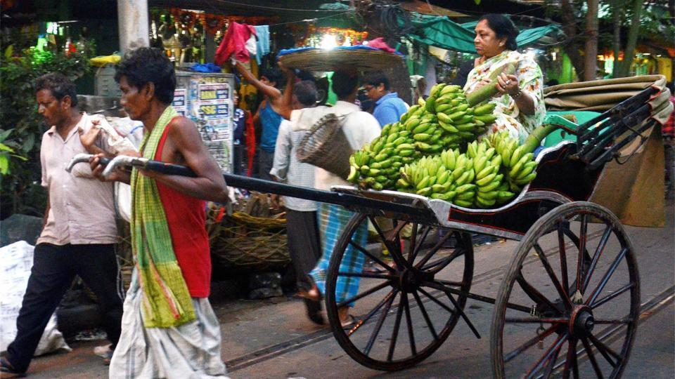 A hand-rickshaw puller ferries an elderly woman carrying bunches of bananas, ahead of Chhath puja festival in Kolkata, West Bengal. (PTI)