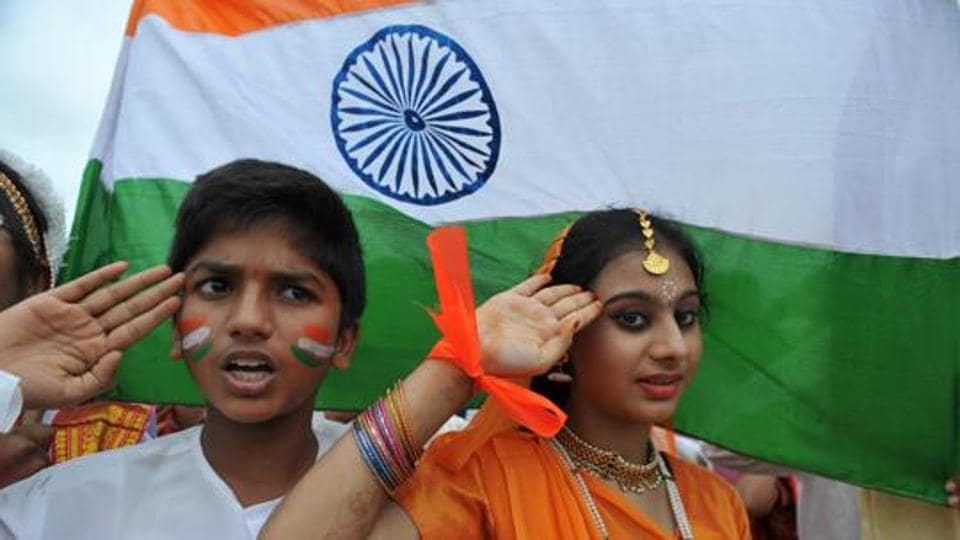 School children salute as they stand to attention and sing the national anthem in Hyderabad,  2016