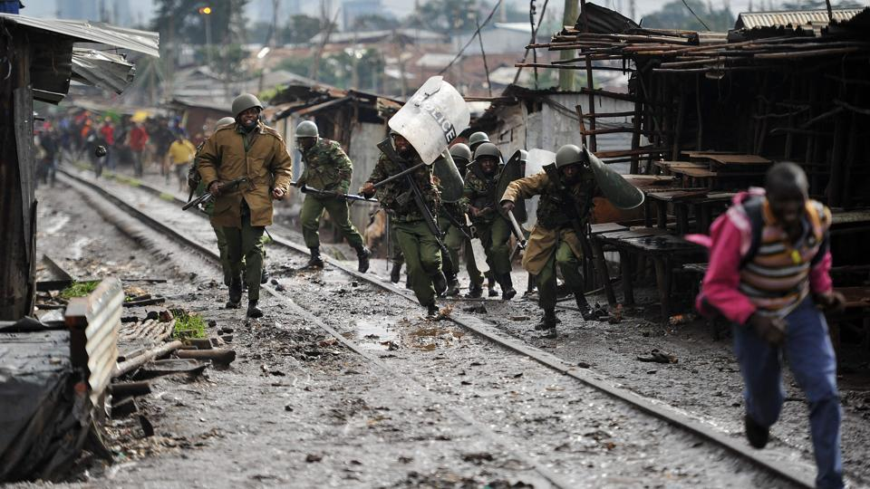 Kenyan police officers, who were caught between bands of stone-throwing residents of Katwekera village within Kibera slum - a stronghold of opposition leader Raila Odinga - charge out in Nairobi on October 26, 2017, as voting in Kenya's repeat presidential poll kicked off on a low turn-out at polling stations in the slum.