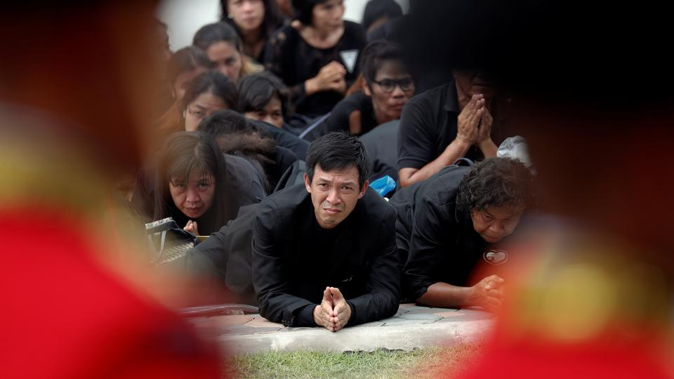 Mourners prostrate as the cremation procession of late King Bhumibol Adulyadej passes by the Grand Palace in Bangkok on October 26, 2017. As the urn passed them, many mourners fully prostrated on the ground, a once abolished practice brought back during Bhumibol's reign, while others burst into tears. (Damir Sagolj / REUTERS)
