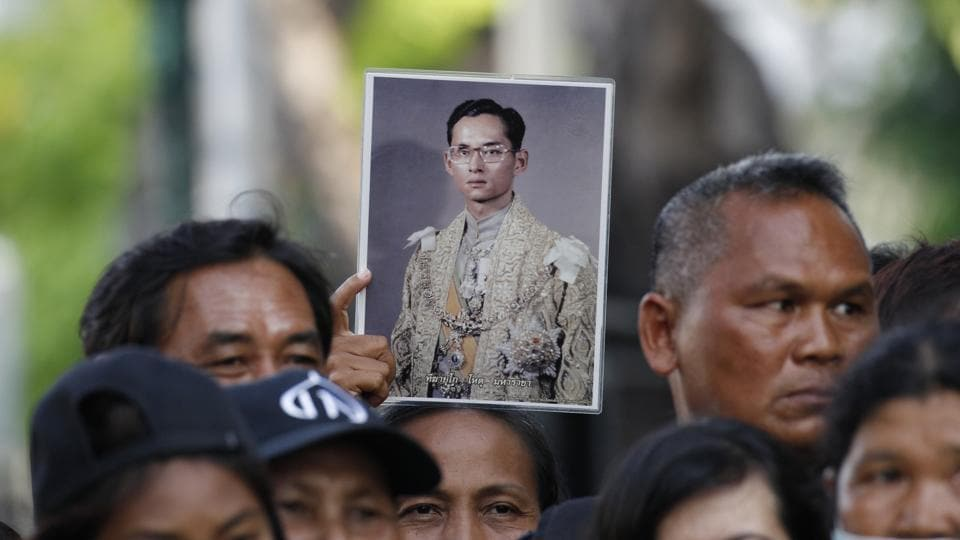 A Thai mourner holds up the portrait of the late King Bhumibol Adulyadej near the Grand Palace to take part in the Royal Cremation ceremony in Bangkok on October 25, 2017. An elaborate five-day funeral is underway for the late king with his son and incumbent ruler performing Buddhist merit-making rites in preparation for moving Bhumibol's remains to a spectacular golden crematorium. (Sakchai Lalit / AP)