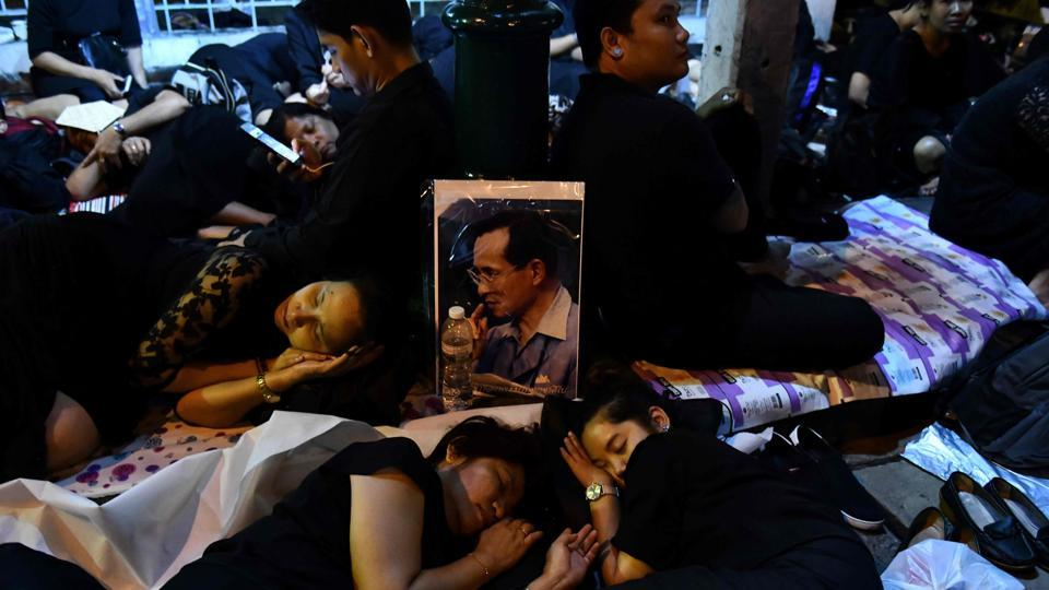 Mourners sleep in front of an image of the late Thai King Bhumibol Adulyadej waiting for his funeral procession on October 26, 2017. About 200,000 black-clad mourners thronged Bangkok's historic quarter before dawn to witness elaborate gilded processions that will be broadcast live. (Anthony Wallace / AFP)