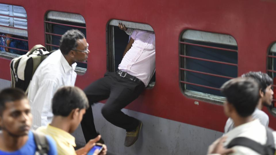 A passenger uses the emergency window to enter the Sampoorna Kranti Express which runs between Patna and New Delhi on Sunday. Massive rush was witnessed at New Delhi railway station as people leave for Bihar and UP for Chhath Puja. (Arvind Yadav/HT Photo)