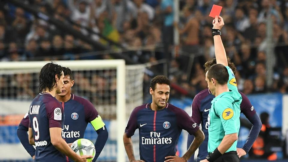 French referee Ruddy Buquet (R) shows a red card to PSG forward Neymar during the Ligue 1 game against Marseille.