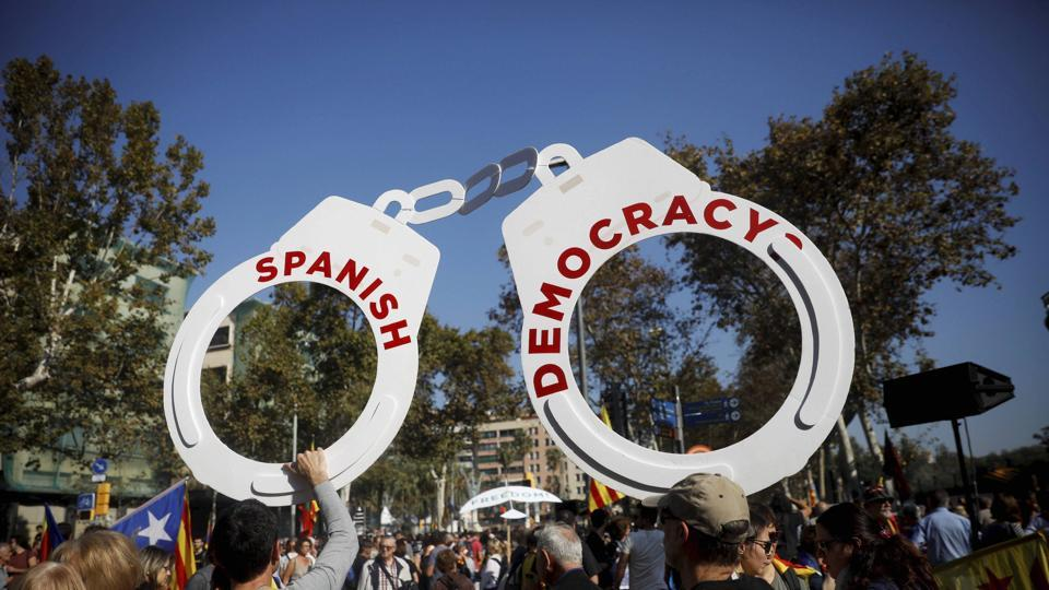 Protesters hold fake handcuffs as they take part a rally outside the Catalan parliament in Barcelona, Spain. (AP Photo)