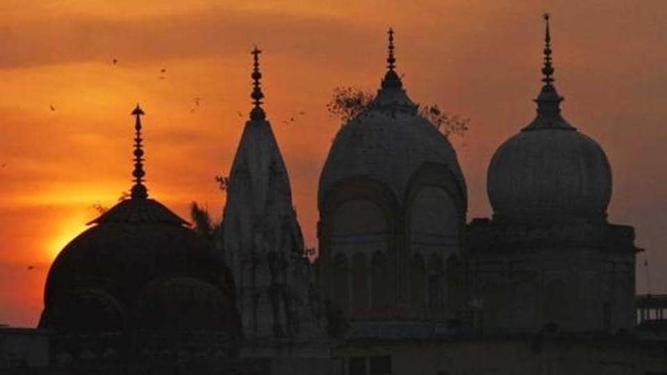 Birds fly at sunset over a temple in Ayodhya.
