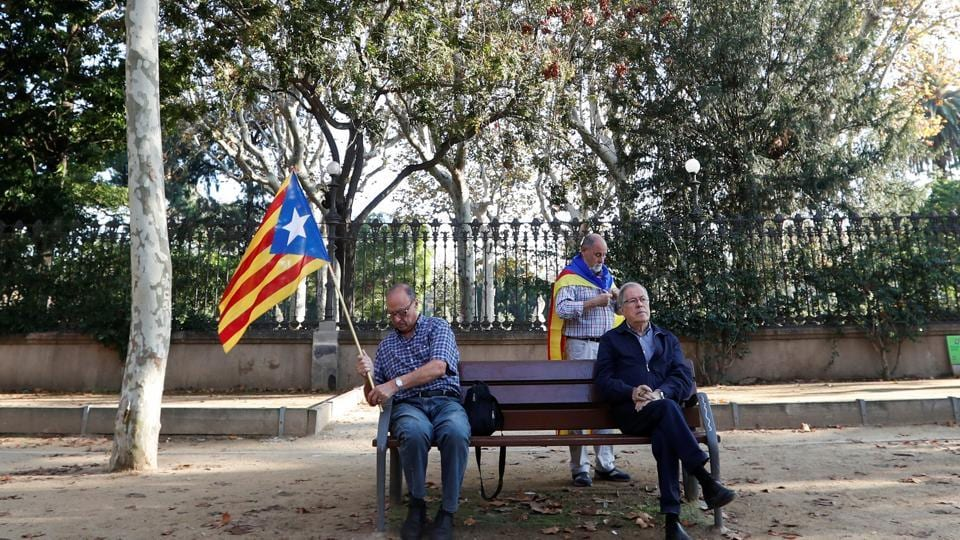 A man holding a Catalan separatist flag sits on a bench outside the Catalan regional parliament in Barcelona, Spain, October 27, 2017.
