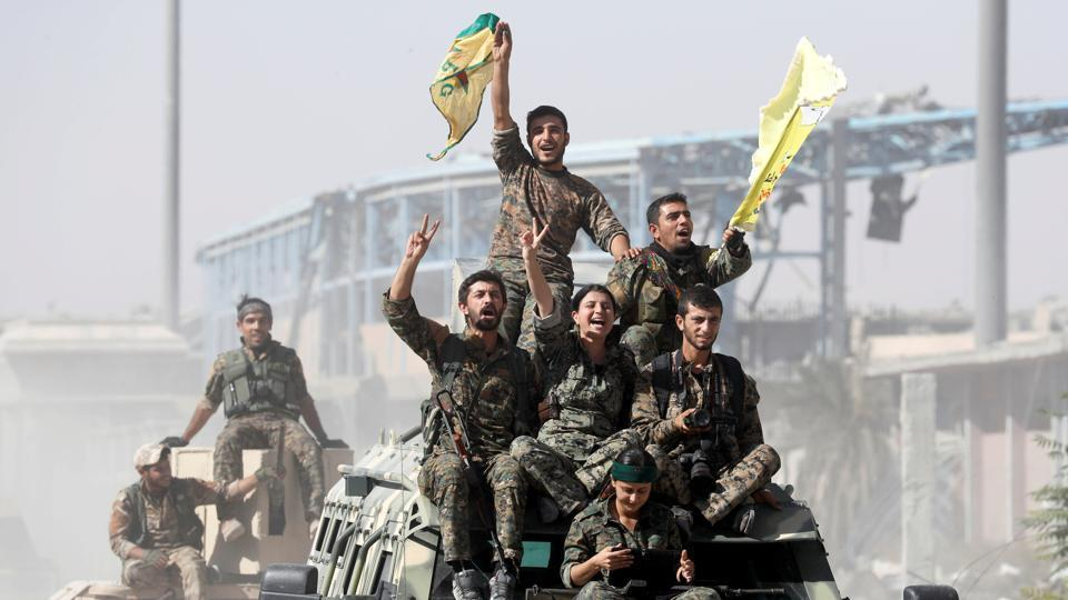 Syrian Democratic Forces fighters ride atop military vehicles as they celebrate victory over Islamic State in Raqqa, Syria, October 17.