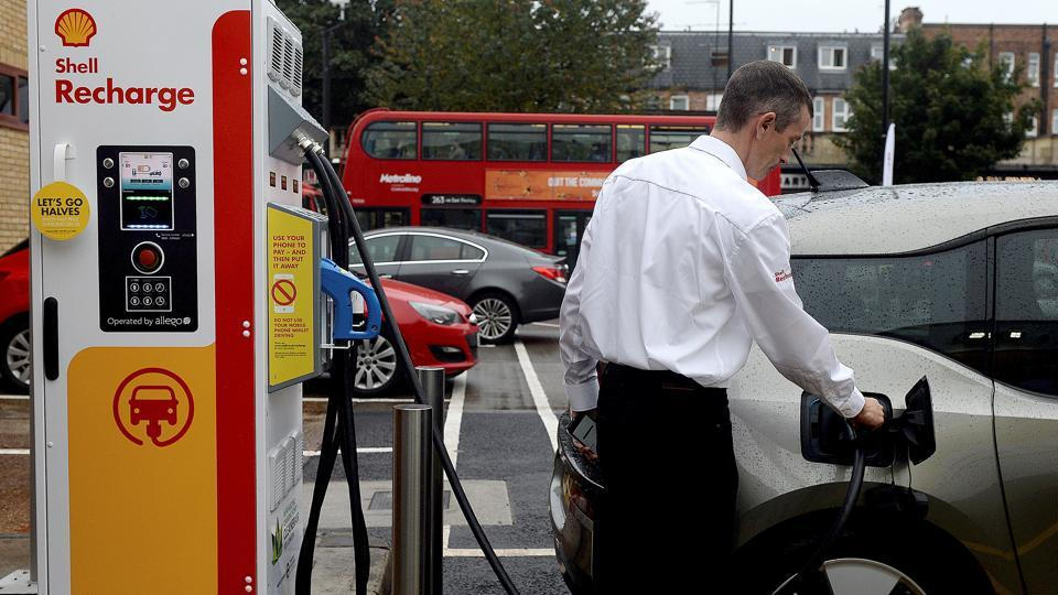 A member of staff charges an electric car at the Holloway Road Shell station where Shell is launching its first fast electric vehicle charging station in London.
