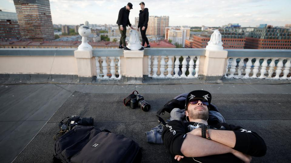 Yevgeny Halkechev of the Rudex team rests as his team mates stand on the parapet of a roof in Moscow, Russia. (Maxim Shemetov / REUTERS)