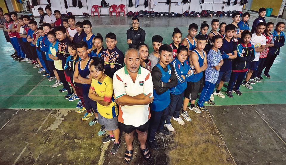 L Ibongcha Singh, who has coached Olympic boxer Mary Kom, among others, strikes a pose with his students at the Khuman Lampka stadium in Imphal. Seen at the back is Dingko, now a full-time coach here.