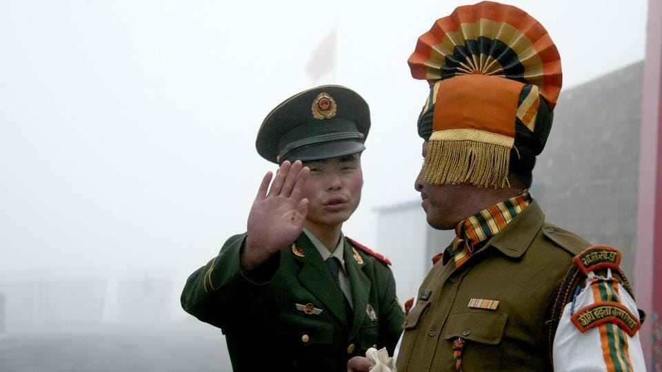 A Chinese soldier (left) gestures next to an Indian soldier at the Nathu La border crossing between India and China in India's northeastern Sikkim state.