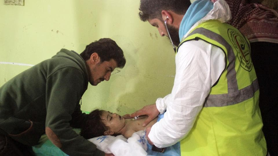 (FILES) This file photo taken on April 4, 2017 shows an unconscious Syrian child receiving treatment at a hospital in Khan Sheikhun, a rebel-held town in the northwestern Syrian Idlib province, following a suspected toxic gas attack.