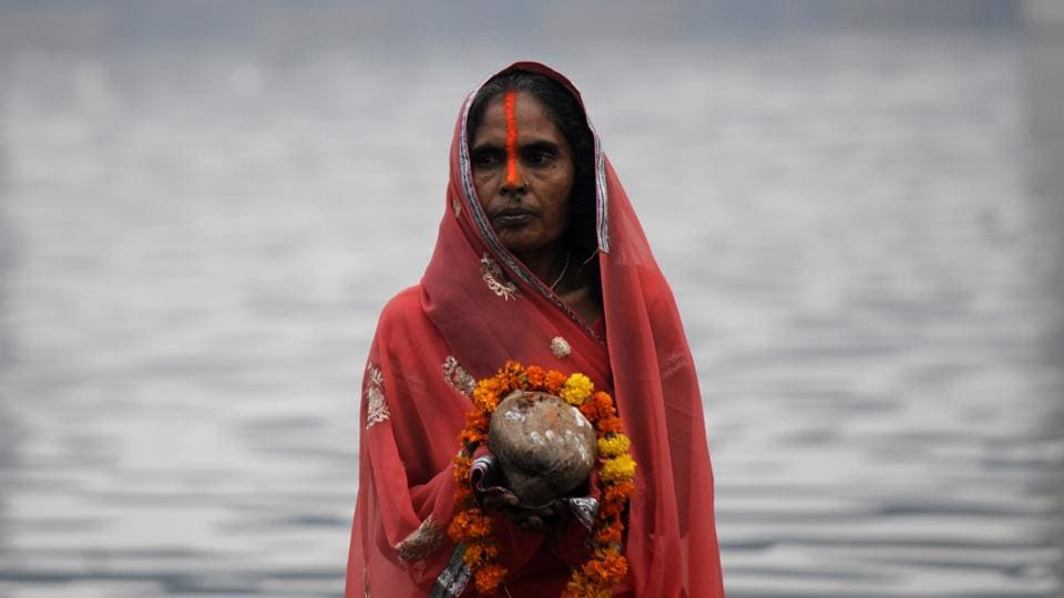A woman offers prayers to the Sun God during sunrise on the 2nd day of Chhath festival at Yamuna ghat , in Noida. On the occasion of the final day of the puja, people converged at river banks before sunrise and offered 'Arghya' to the rising sun in wicker baskets. (Sunil Ghosh / HT Photo)