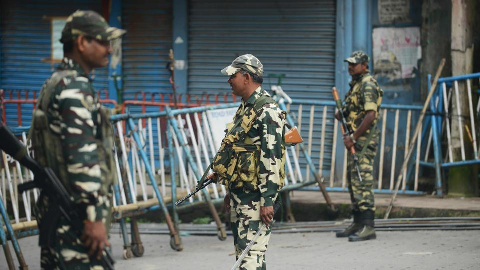 Paramilitary forces stand guard along a road during the 83th day of an indefinite strike called by the Gorkha Janmukti Morcha in Kalimpong on September 3, 2017.