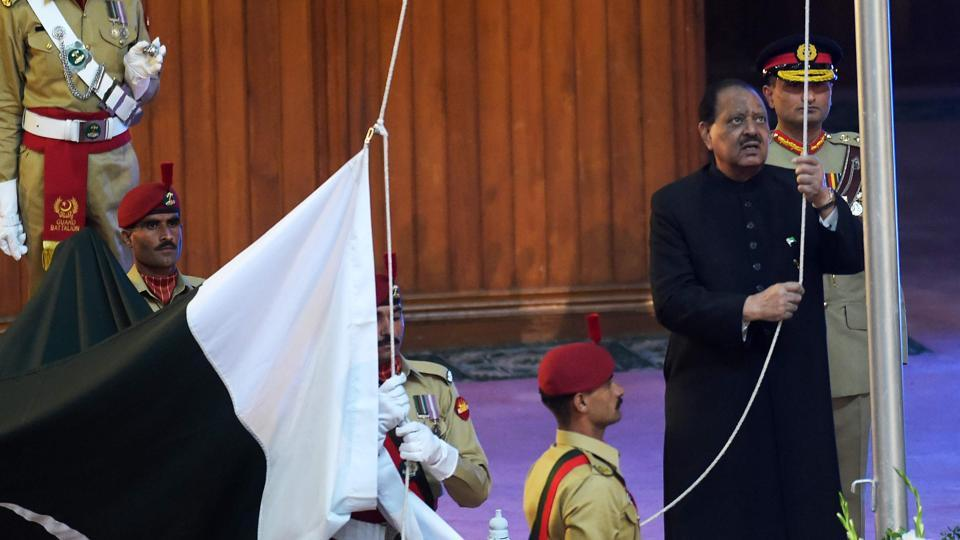 Pakistan's President Mamnoon Hussain (right) hoists the national flag during a ceremony to mark the country's Independence Day in Islamabad on August 14, 2017.