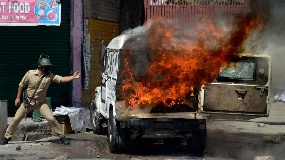 A policeman stands next to a police vehicle set ablaze by protesters in Anantnag district of South Kashmir .