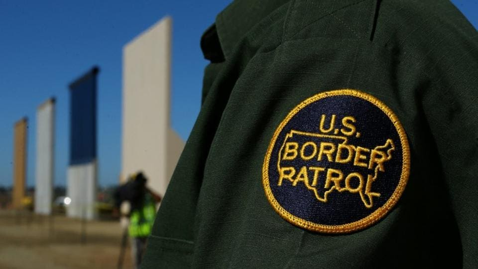 A border patrol officer stands along the US- Mexico border.