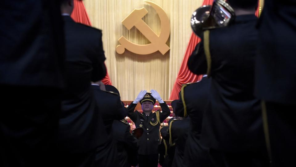 A Chinese People's Liberation Army (PLA) officer practices conducting a military band before the opening session of the Chinese Communist Party's five-yearly Congress at the Great Hall of the People in Beijing on October 18, 2017.