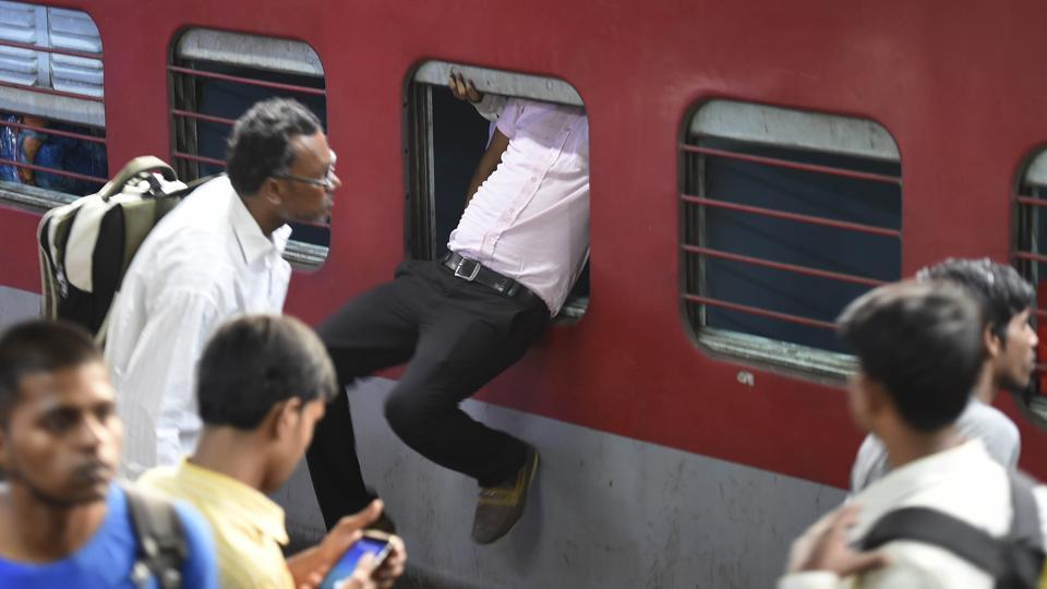 A passenger uses the emergency window to enter the Sampoorna Kranti Express, which runs between Patna and New Delhi on Sunday. Massive rush was witnessed at New Delhi railway station as people left for Bihar and UP on the occasion of Chhath Puja. (Arvind Yadav / HT Photo)