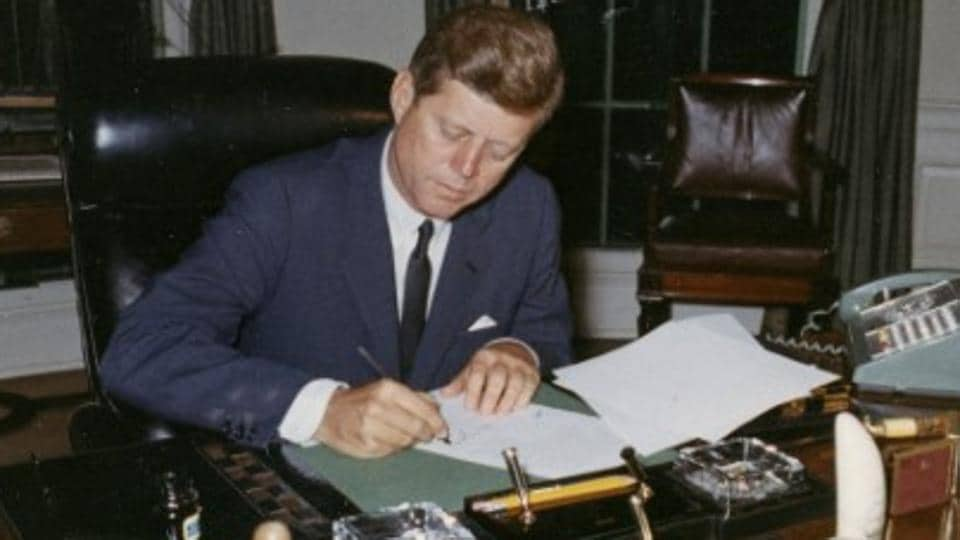 US President John F Kennedy signs a proclamation for the interdiction of the delivery of offensive weapons to Cuba during the Cuban missile crisis, at the White House in Washington, DC.