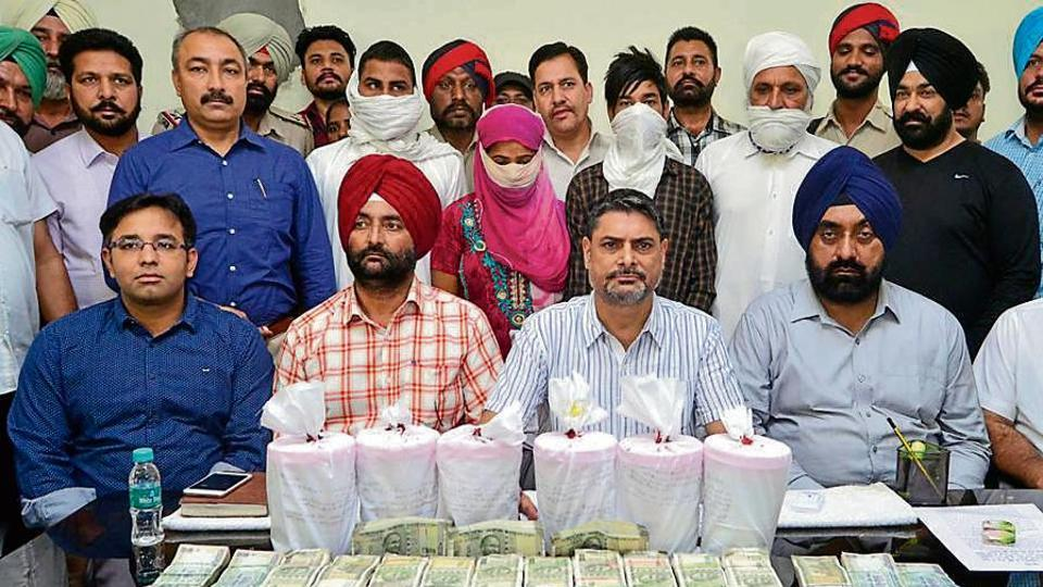 Special Task Force AIG Rashpal Singh (2nd from right) and other officials with the accused (covered faces), seized currency and 6kg heroin in Amritsar on Friday.