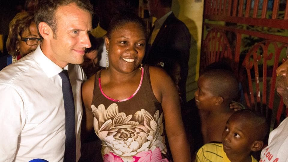 French President Emmanuel Macron poses with a woman during a visit to the Crique neighborhood, in Cayenne, French Guiana, Friday.