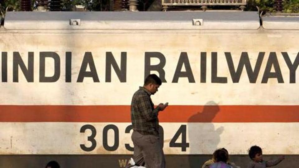A train engine moves past waiting travellers at a railway station in New Delhi. (AFP FILEPhoto)